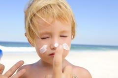 Niño lindo con la protección solar en la playa Fotos de archivo