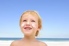 Niño lindo con la protección solar en la playa Imagenes de archivo