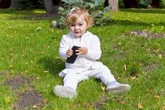 Niño lindo con la sentada celular en hierba verde imagenes de archivo