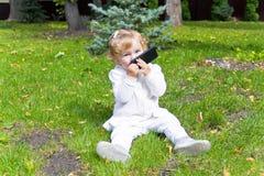 Niño lindo con la sentada celular en hierba verde fotos de archivo libres de regalías