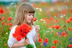 Niño lindo con las amapolas en el campo floreciente Imágenes de archivo libres de regalías