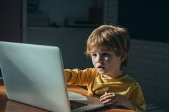 Niño lindo del colegial que juega y que practica surf en línea tarde en la noche El niño enviciado a los juegos de Internet y los fotografía de archivo