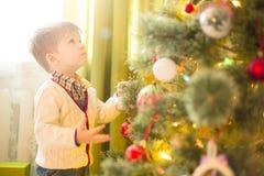 Niño lindo del niño pequeño que adorna el árbol de navidad en sitio Día de fiesta de la Navidad o del Año Nuevo Fotografía de archivo