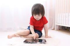 Niño lindo en camiseta roja con la tableta Imágenes de archivo libres de regalías