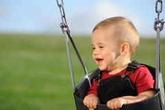 Niño lindo en el oscilación del patio Imagen de archivo