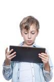 Niño lindo en la camisa azul que sostiene una tableta Imagen de archivo libre de regalías
