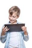 Niño lindo en la camisa azul que sostiene una tableta Fotos de archivo