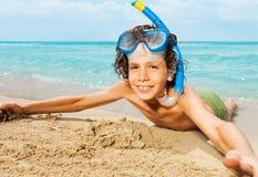 Niño lindo en la máscara del equipo de submarinismo que pone en la playa arenosa Imágenes de archivo libres de regalías