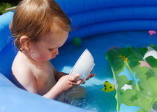 Niño lindo en piscina azul Foto de archivo