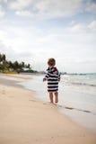 Niño lindo en un encubrimiento rayado de la playa fotos de archivo