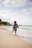 Niño lindo en un encubrimiento rayado de la playa fotografía de archivo libre de regalías