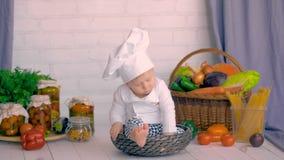Niño lindo feliz en sombrero del ` s del cocinero en la risa de la cocina, jugando
