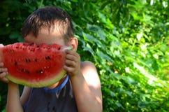 Niño lindo feliz que come la sandía en el jardín imagen de archivo libre de regalías