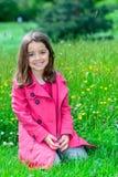 Niño lindo feliz que se sienta en un jardín de flores Imagen de archivo