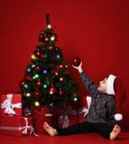 Niño lindo que adorna el árbol de navidad con las gotas rojas fotos de archivo