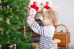 Niño lindo que adorna el árbol de navidad, interior Fotografía de archivo