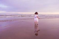 Niño lindo que camina a lo largo de una playa en puesta del sol fotografía de archivo