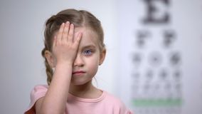 Niño lindo que cierra un ojo para probar la agudeza visual, diagnósticos de la enfermedad de la vista almacen de metraje de vídeo