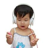 Niño lindo que escucha la música en los auriculares y el goce Imagenes de archivo