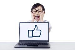 Niño lindo que grita con el ordenador portátil en el escritorio Imagenes de archivo