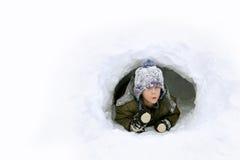 Niño lindo que juega afuera en fuerte de la nieve del invierno Fotografía de archivo
