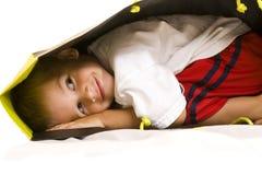 Niño lindo que juega con un bolso de compras Imagen de archivo