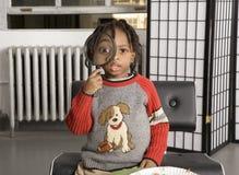 Niño lindo que juega con una lupa foto de archivo