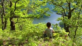 Niño lindo que juega en el paisaje del destino del lago almacen de video