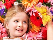 Niño lindo que miente en la flor. foto de archivo