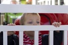 Niño lindo que mira fuera del cercado del alambre bloqueado outdoors fotografía de archivo libre de regalías