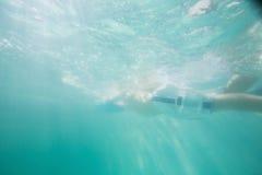 Niño lindo que nada bajo el agua en piscina Imagenes de archivo
