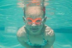 Niño lindo que presenta bajo el agua en piscina Fotos de archivo