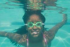Niño lindo que presenta bajo el agua en piscina Imagen de archivo