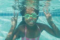 Niño lindo que presenta bajo el agua en piscina Foto de archivo