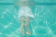 Niño lindo que presenta bajo el agua en piscina Imagenes de archivo