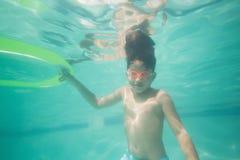 Niño lindo que presenta bajo el agua en piscina Fotografía de archivo