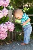 Niño lindo que se coloca en la grava en un parque Foto de archivo libre de regalías