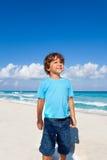 Niño lindo que se coloca en la playa arenosa de la costa Foto de archivo
