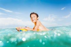 Niño lindo que se divierte en el mar en tablero del cuerpo Imagen de archivo libre de regalías