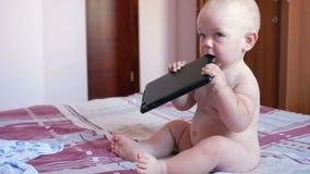 Niño lindo que se sienta en cama y las historietas de las miradas fijas en la tableta Bebé anual minúsculo sin la ropa almacen de video