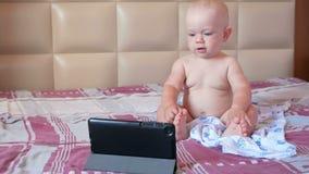 Niño lindo que se sienta en cama y las historietas de las miradas fijas en la tableta Bebé anual minúsculo sin la ropa almacen de metraje de vídeo