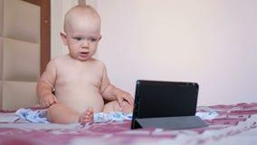 Niño lindo que se sienta en cama y las historietas de las miradas fijas en la tableta Bebé anual minúsculo sin la ropa metrajes