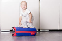 Niño lindo que se sienta en la maleta y que mira la cámara Bebé divertido que va a vacation Fotografía de archivo