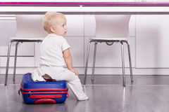 Niño lindo que se sienta en la maleta y que mira la cámara Bebé divertido que va a vacation Imagenes de archivo
