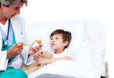 Niño lindo que toma la medicina de la tos Foto de archivo