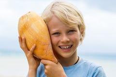 Niño lindo, sonriente que lleva a cabo la cáscara de la prensa al oído Imagen de archivo