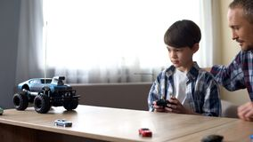 Niño lindo y su coche controlado de radio de funcionamiento del padre en casa, tecnologías imagen de archivo libre de regalías