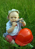 Niño maravilloso con un casco anaranjado y una llave Foto de archivo libre de regalías