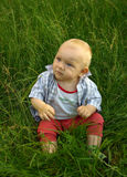 Niño maravilloso que se sienta en hierba verde Fotos de archivo libres de regalías