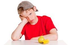 Niño masculino aburrido con la fruta Foto de archivo libre de regalías